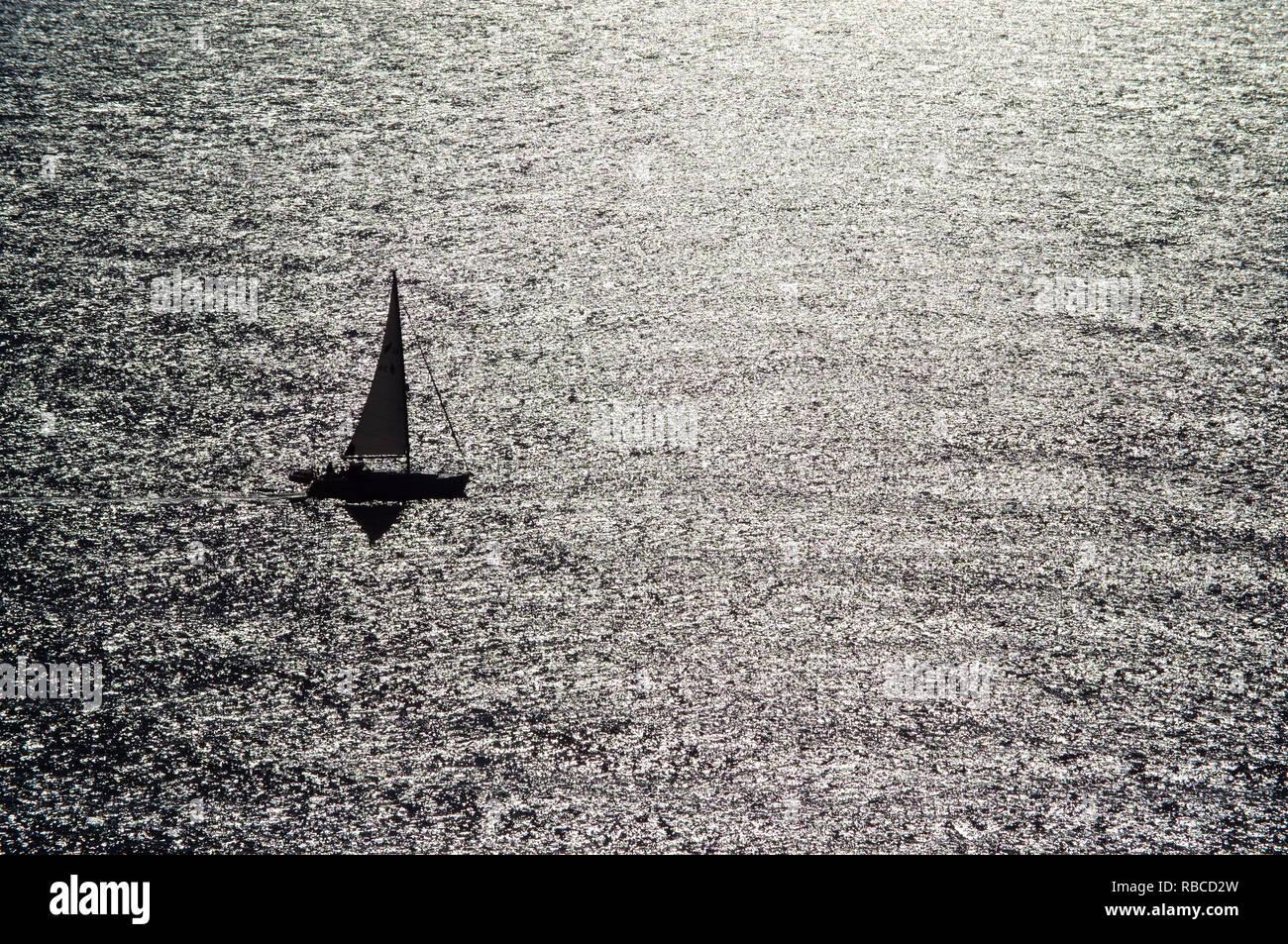 Small sailing boat on shining sea. - Stock Image