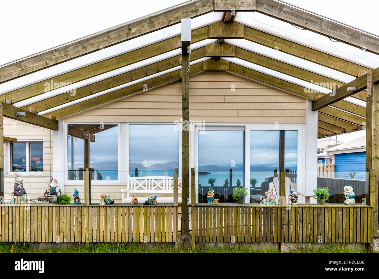 Hofn, Iceland - June 15, 2018: Closeup of wooden house in small fishing village with reflection of blue fjord river water - Stock Image