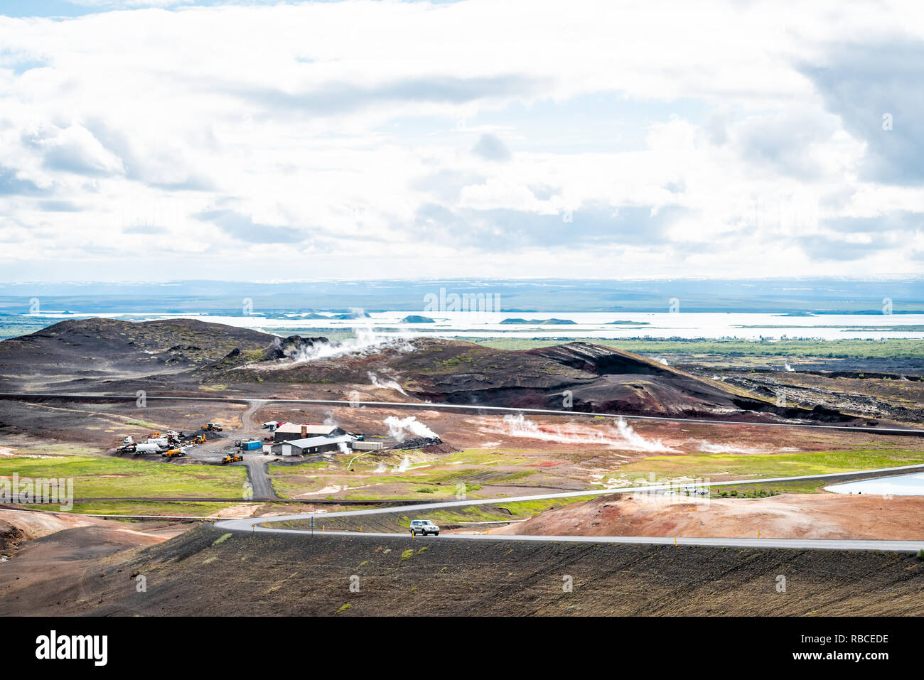 Reykjahlid, Iceland - June 16, 2018: Landscape high angle view of lake Myvatn and fumaroles steam vents during cloudy day and car on road highway - Stock Image