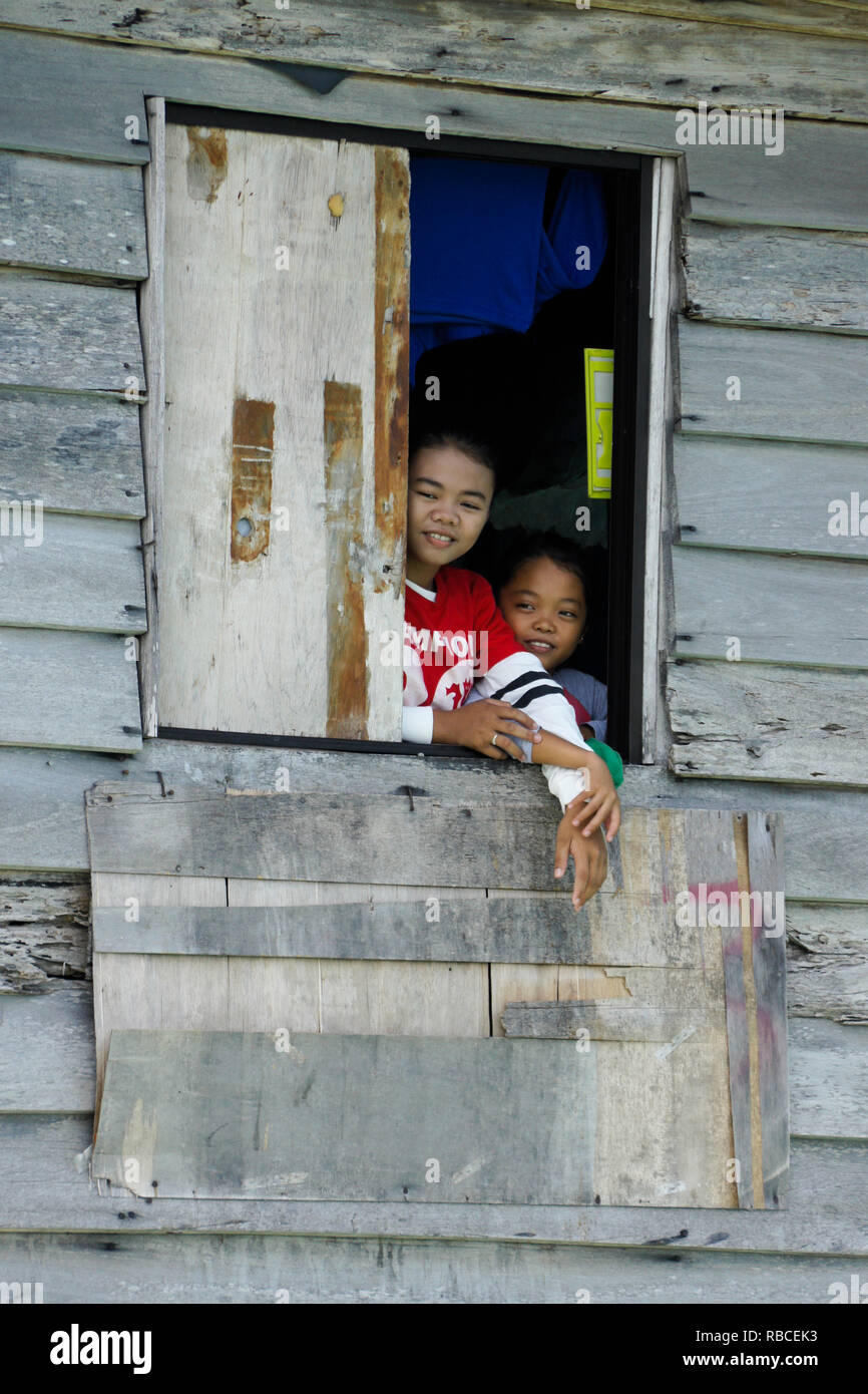 Children looking out window of shack in stilt village, South China Sea near Kota Kinabalu, Sabah (Borneo), Malaysia - Stock Image