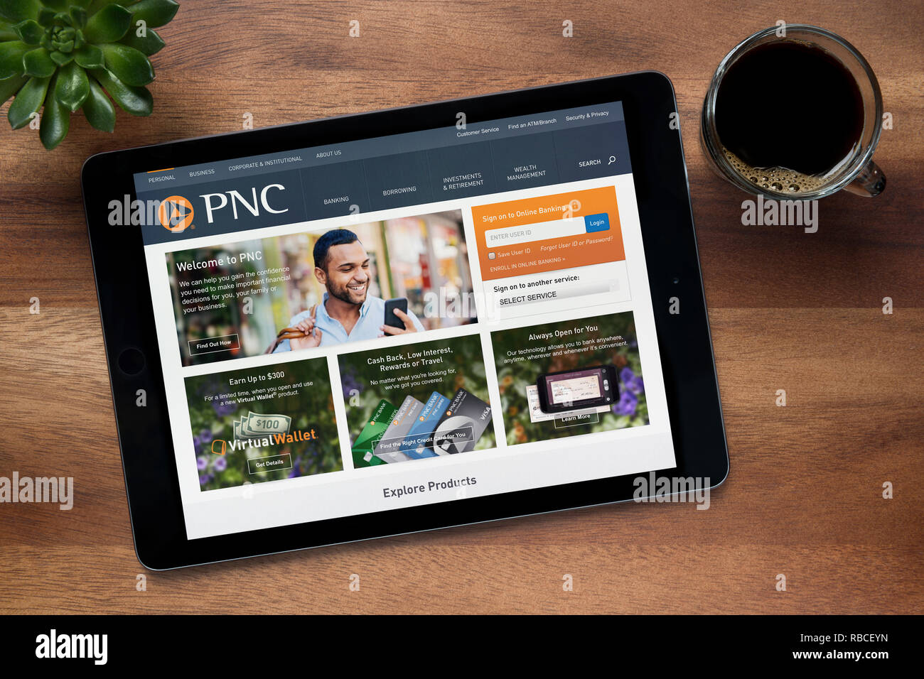 The website of PNC Financial Services is seen on an iPad tablet, on a wooden table along with an espresso coffee and a house plant (Editorial only) - Stock Image