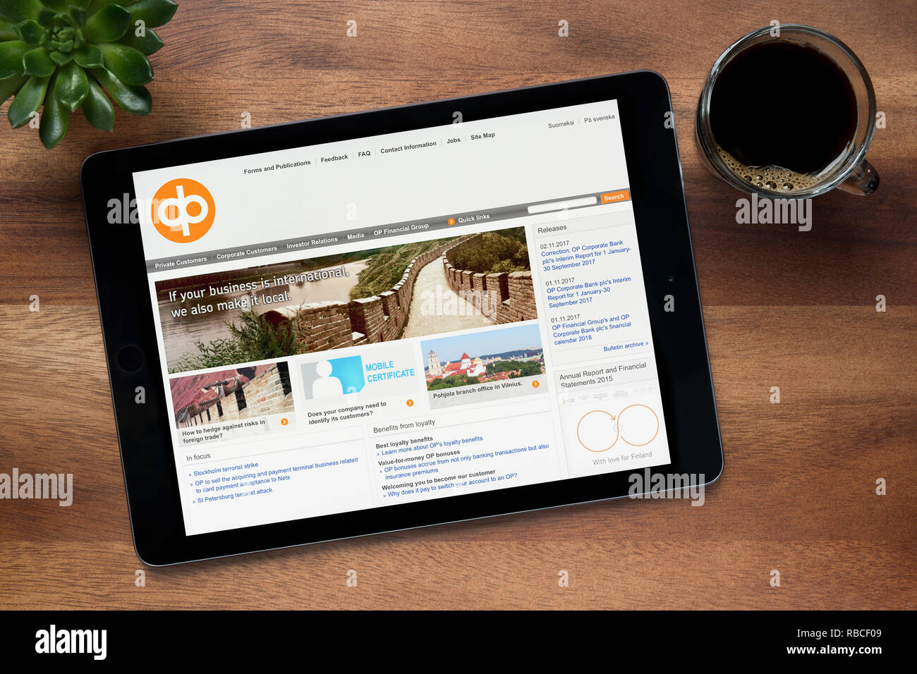The website of OP Financial Group (OP-Pohjola) is seen on an iPad tablet, resting on a wooden (Editorial use only). - Stock Image