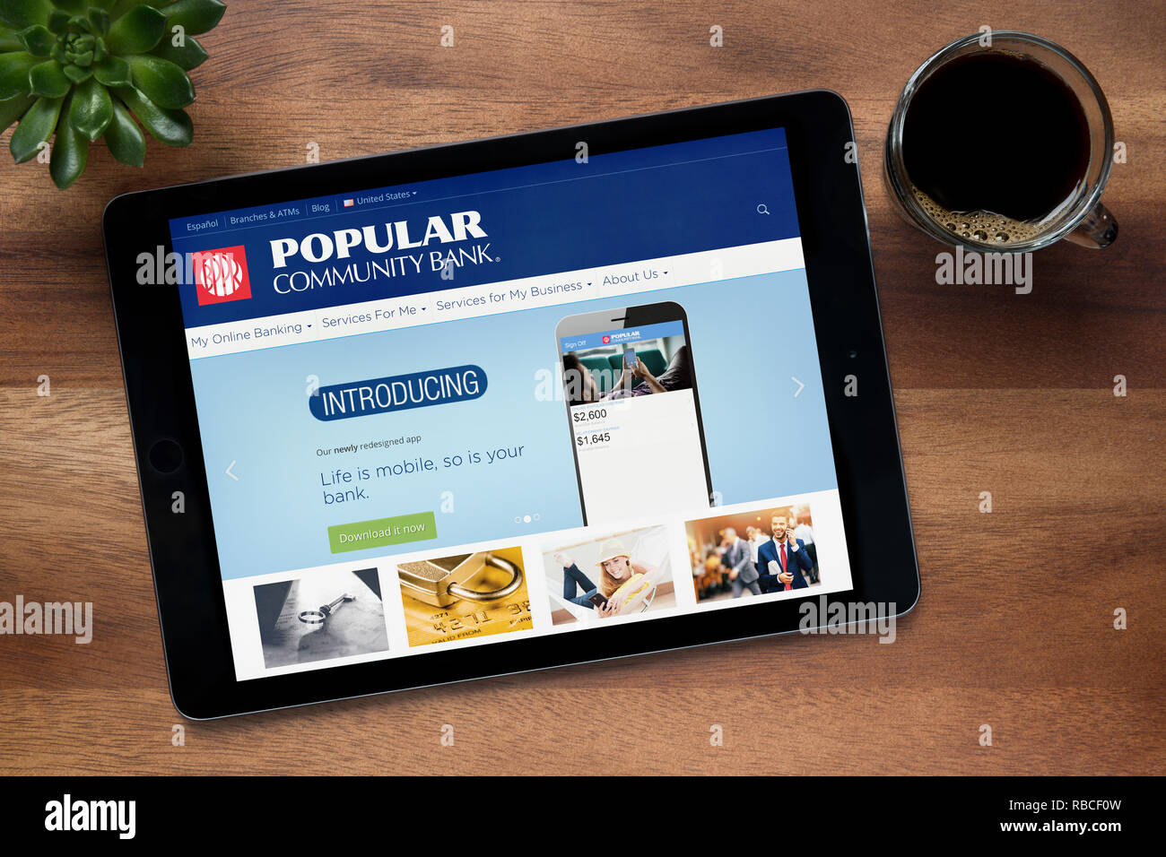 The website of Popular Community Bank is seen on an iPad tablet, resting on a wooden (Editorial use only). - Stock Image