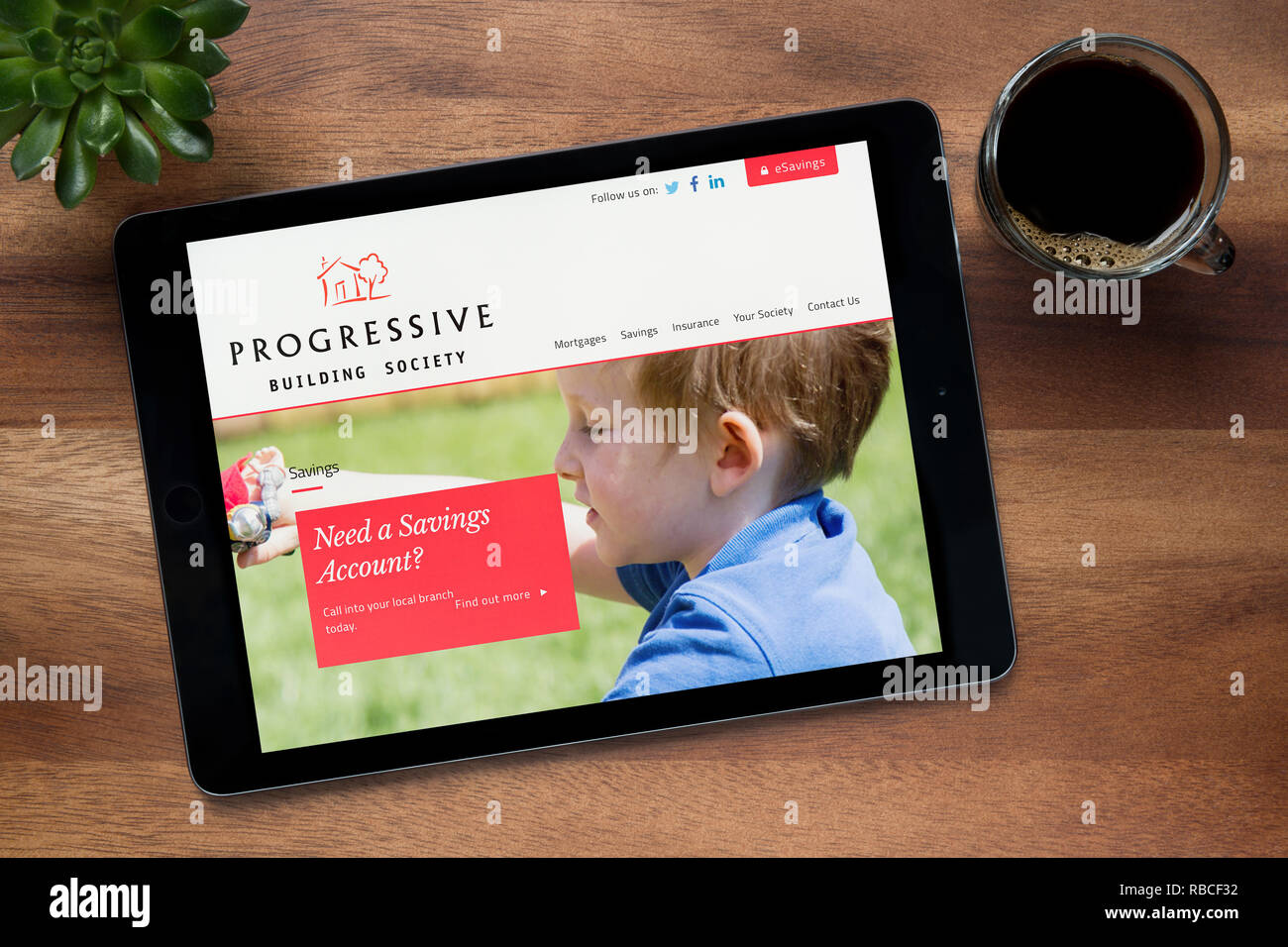 The website of Progressive Building Society is seen on an iPad tablet, resting on a wooden (Editorial use only). - Stock Image