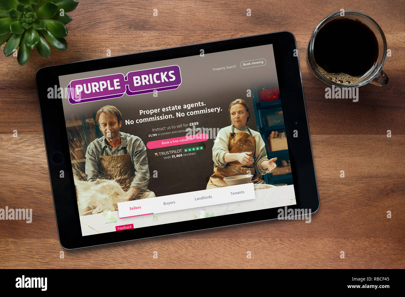 The website of Purple Bricks is seen on an iPad tablet, on a wooden table along with an espresso coffee and a house plant (Editorial use only). - Stock Image