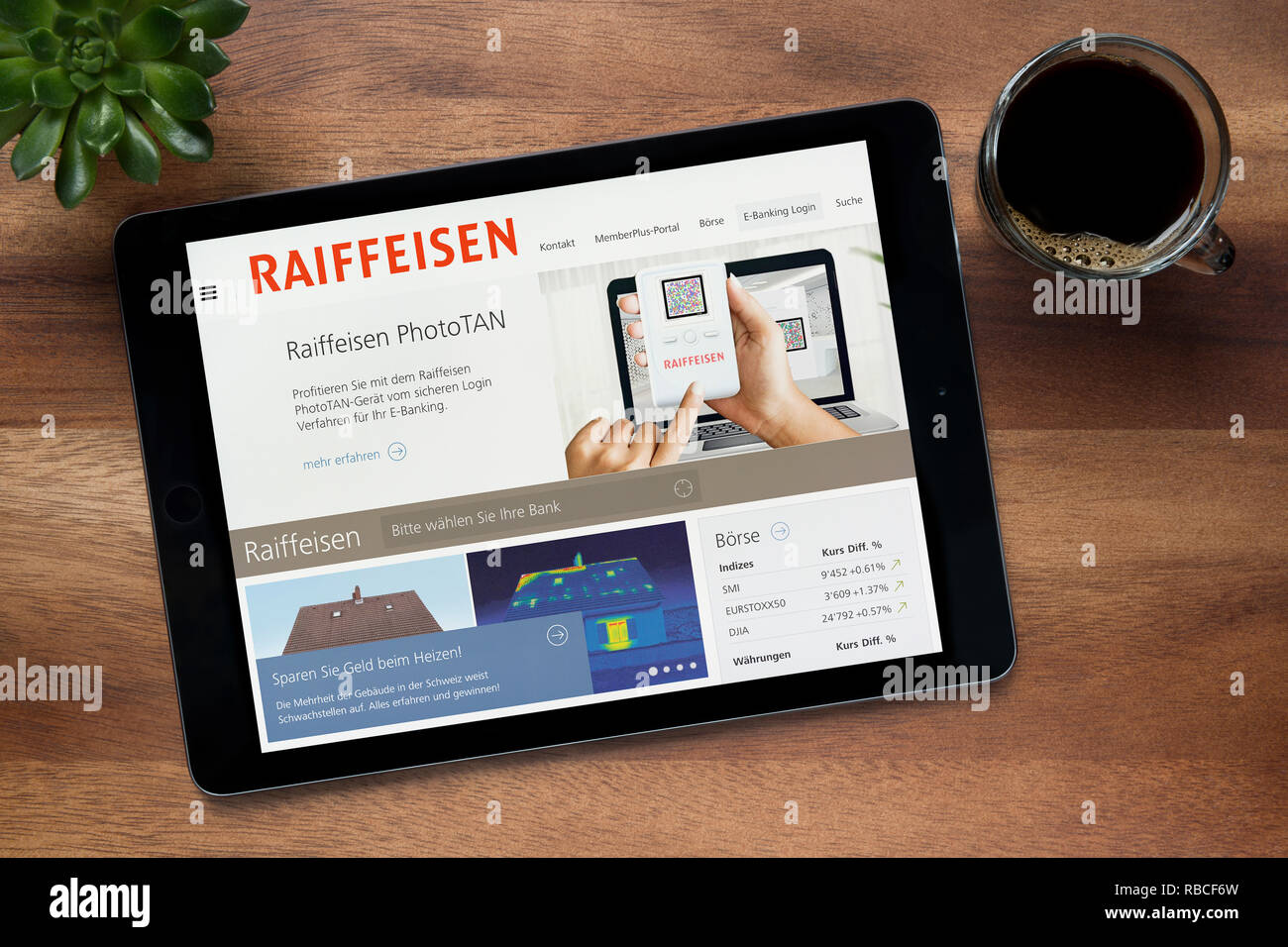 The website of the Swiss bank, Raiffeisen, is seen on an iPad tablet, resting on a wooden (Editorial use only). - Stock Image