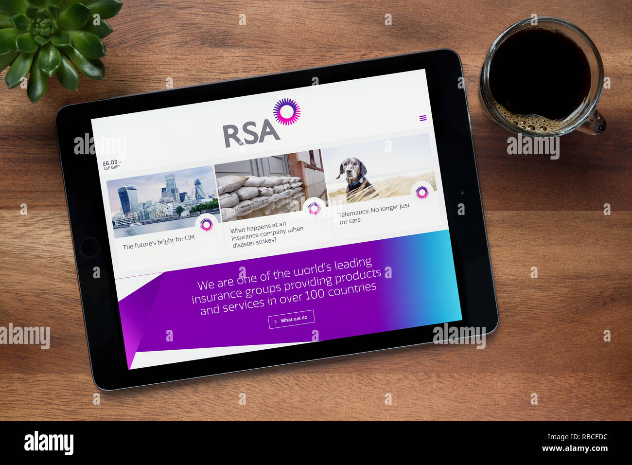The website of RSA (Royal & Sun Alliance) is seen on an iPad tablet, resting on a wooden (Editorial use only). - Stock Image