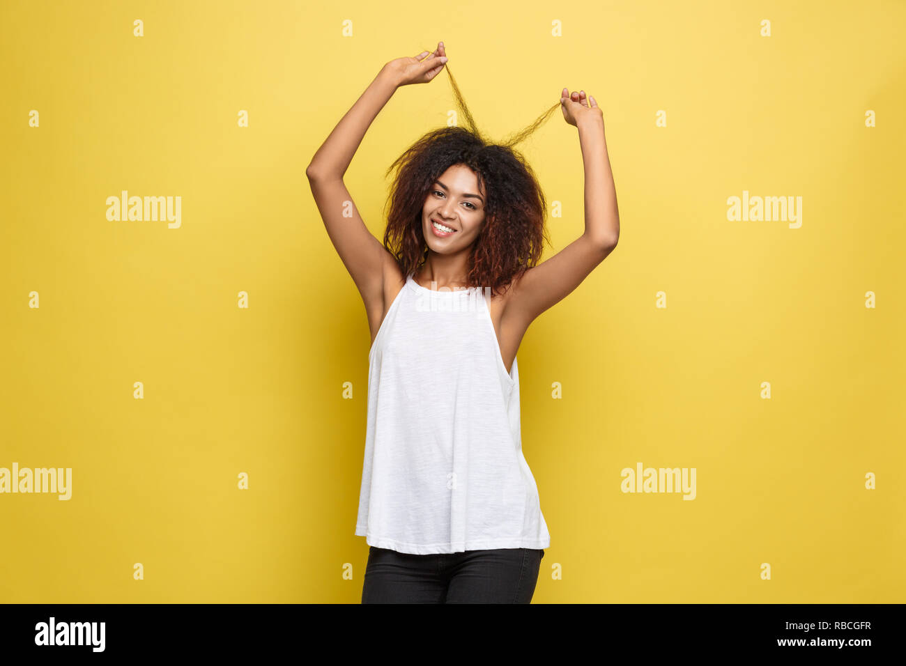 Beautiful attractive African American woman posting play with her curly afro hair. Yellow studio background. Copy Space - Stock Image