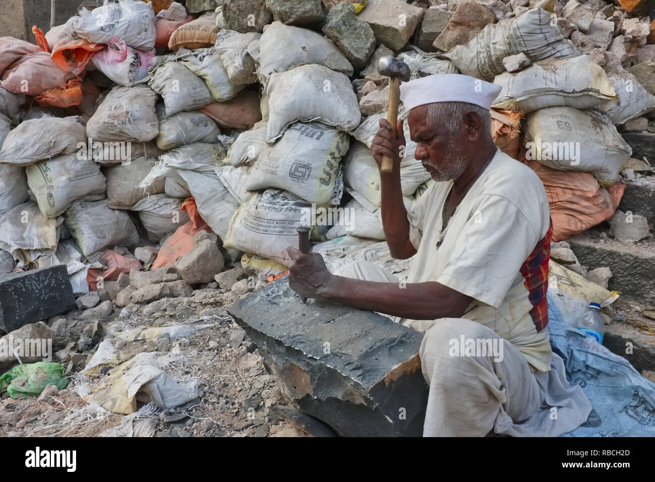 A stonemason in Mumbai, India, carves out a stone from a piece of granite; working w/o protection, many stonemasons risk black lung and eye injuries - Stock Image