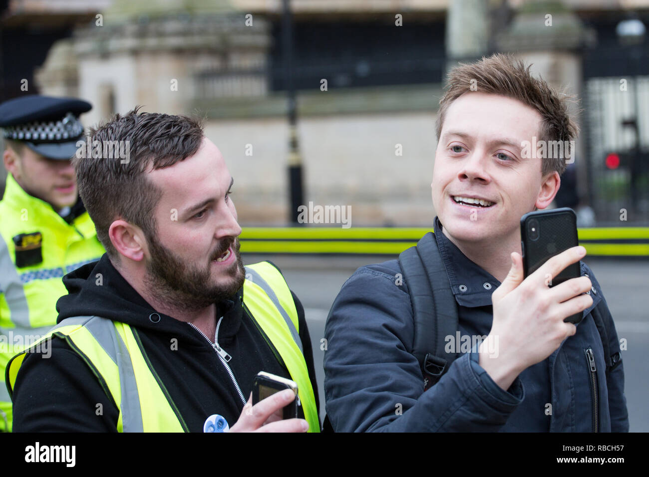 James Goddard follows Owen Jones outside the Houses of Parliament - Stock Image