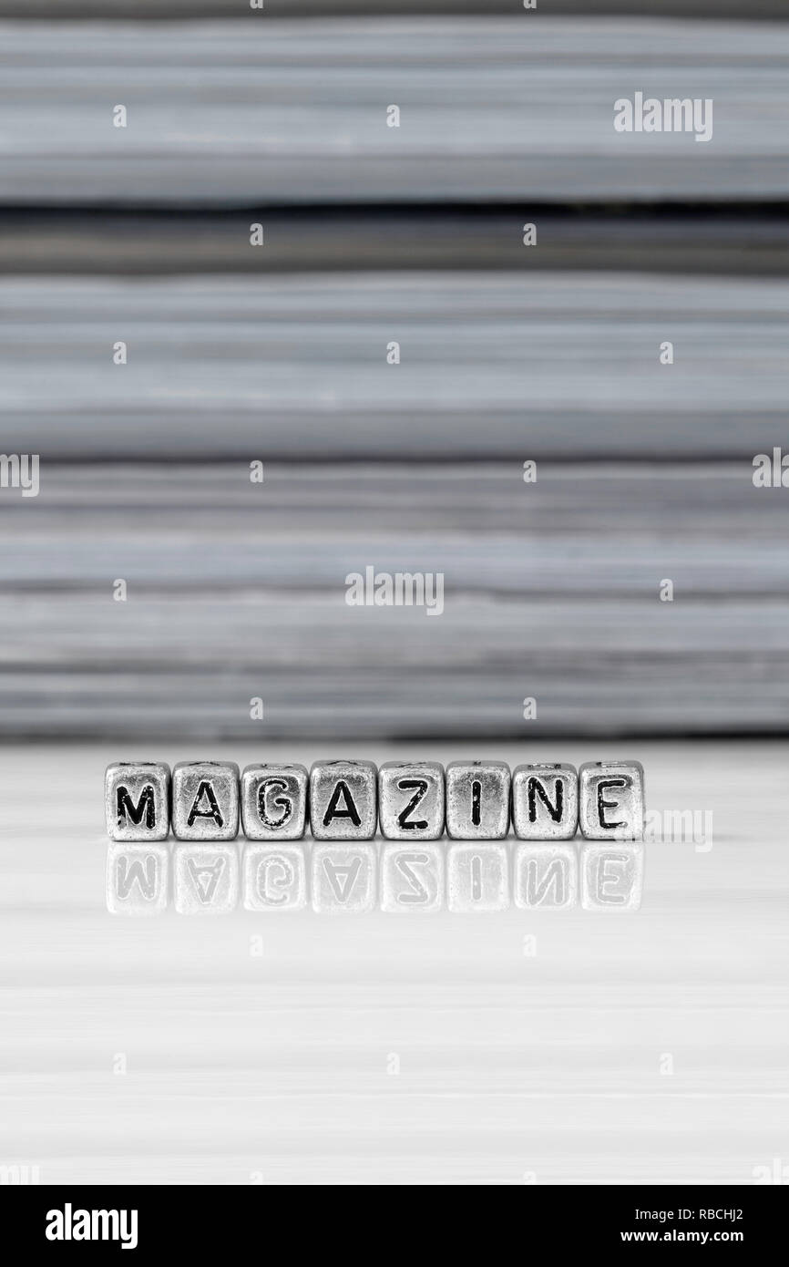 Magazine on beads with magazines stacked in the background reflected on a white surface - Stock Image