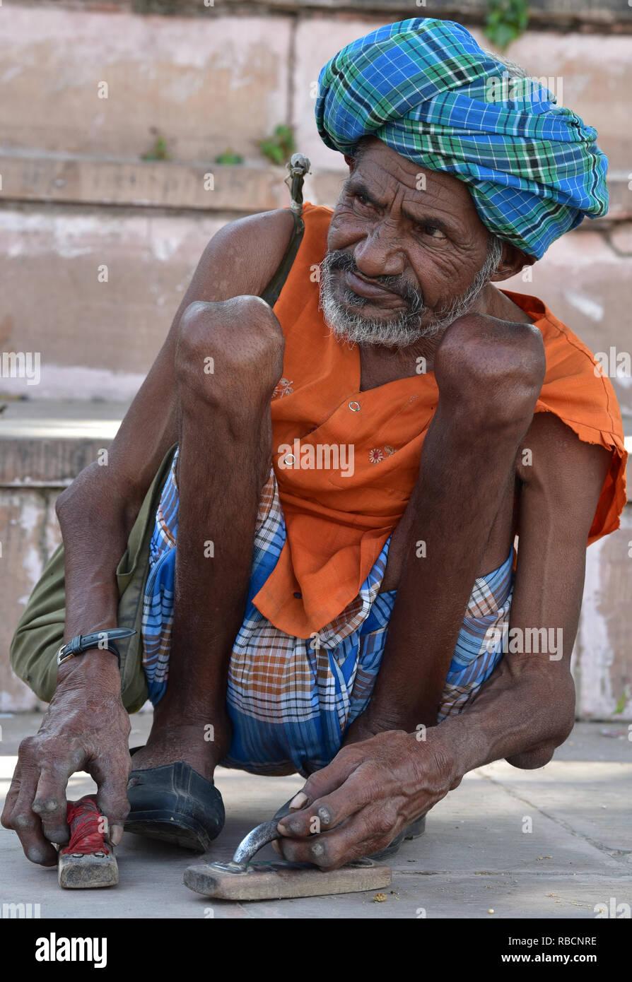 Indian man crouching on the banks of the holy Pushkar Lake, Rajasthan, Western India, Asia. - Stock Image