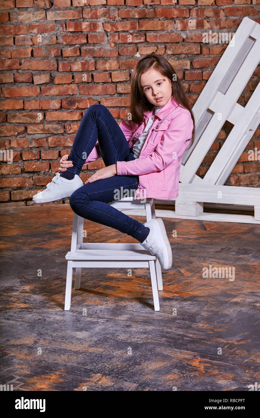 Stylish Child Girl Sitting Fashion Pose On Chair