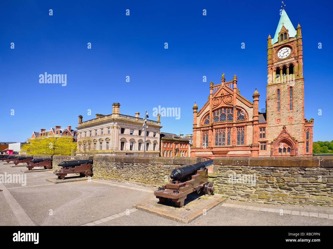 Northern Ireland, County Derry, The Guild Hall, view from the city's 17th century walls with a row of cannons in the foreground. - Stock Image