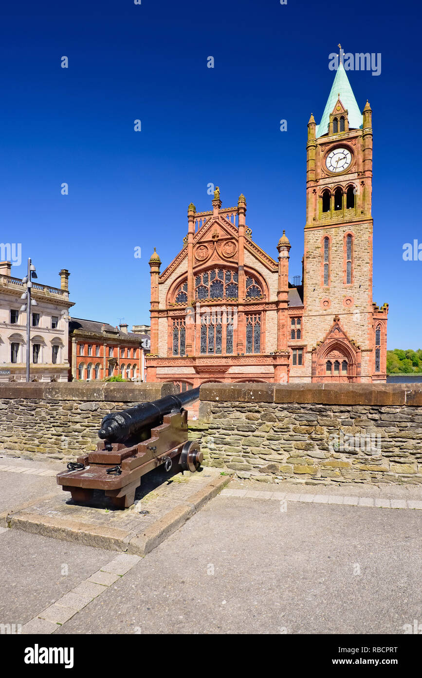 Northern Ireland, County Derry, The Guild Hall, view from the city's 17th century walls with a cannon in the foreground. - Stock Image