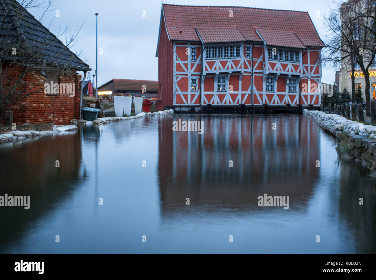 Wismar, Germany. 09th Jan, 2019. The Red House at the city harbour is in high water which accumulates in the fresh pit. A storm surge is expected again in many places on the Baltic Sea coast in the northeast. The Hamburg maritime weather service issued a strong wind warning for the Baltic coast. Credit: Jens Büttner/dpa-Zentralbild/dpa/Alamy Live News - Stock Image