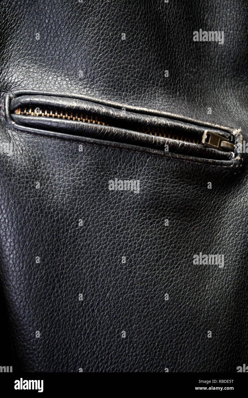 Close up of old black leather motorcycle jacket focusing on zippered pocket. - Stock Image