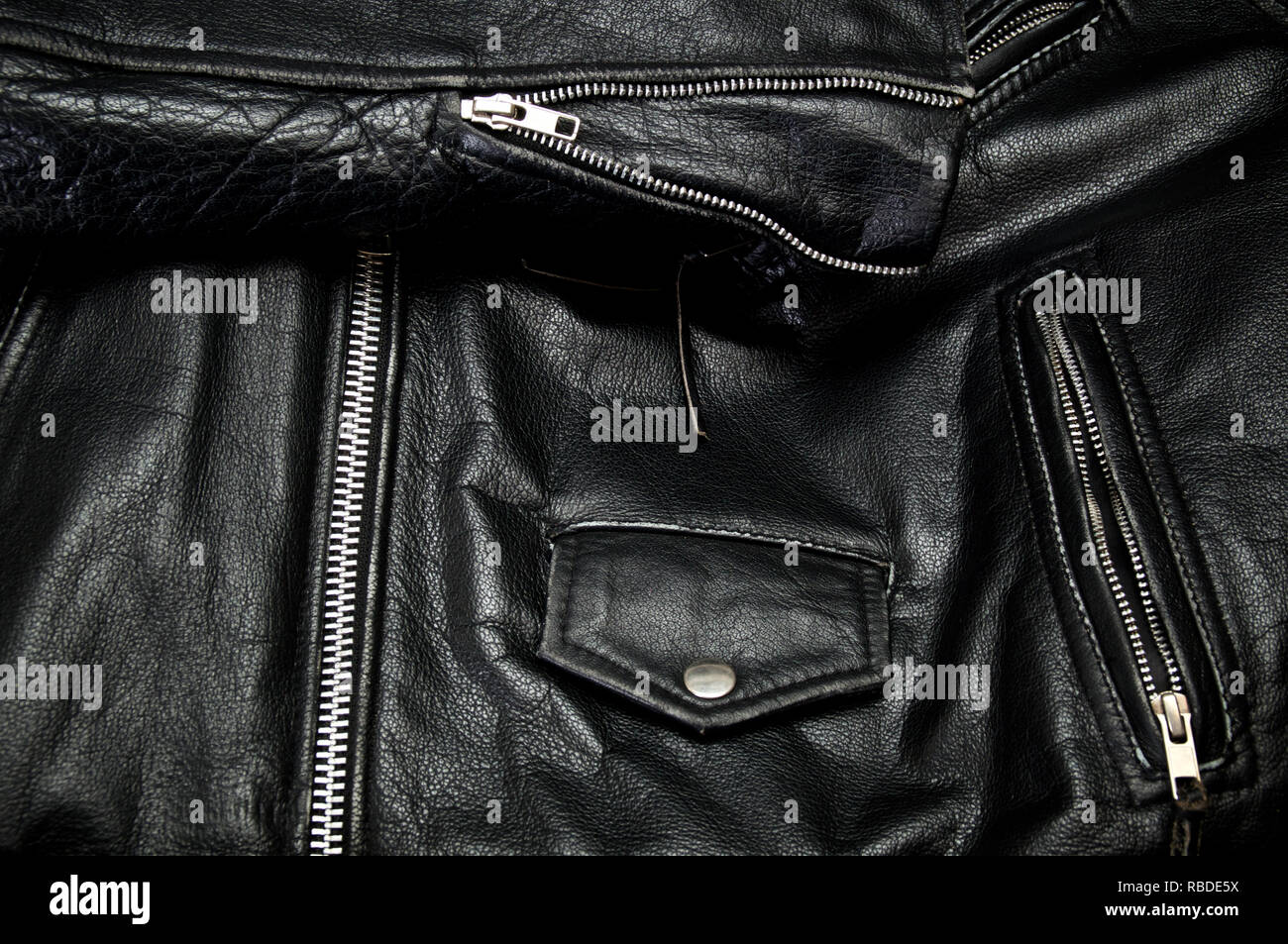Detail of old black leather police style motorcycle jacket focusing on zippers and  pockets. - Stock Image
