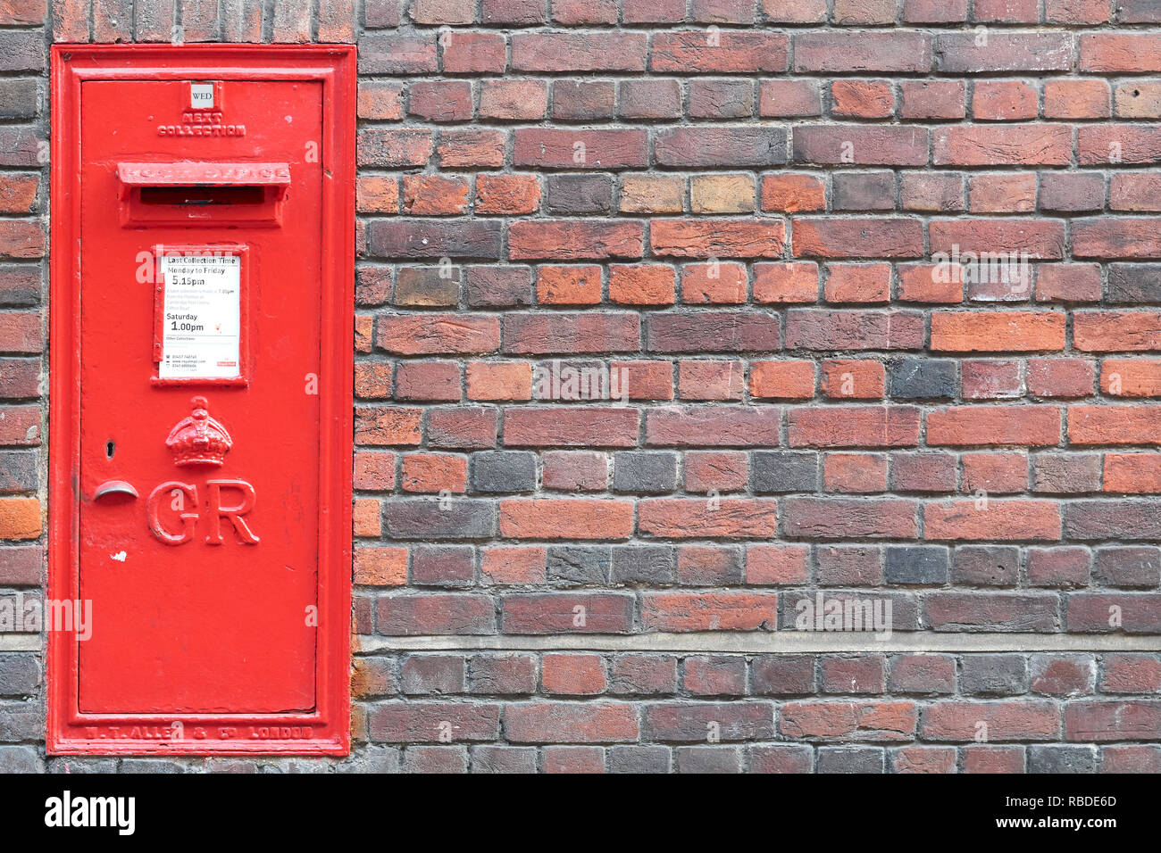 Red post box recessed in an ouside brick wall of Sidney Sussex college, Cambridge university, England. - Stock Image