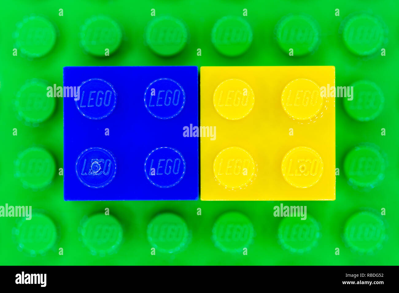 Blue and yellow 2x2 Lego bricks on a green Lego base - Stock Image