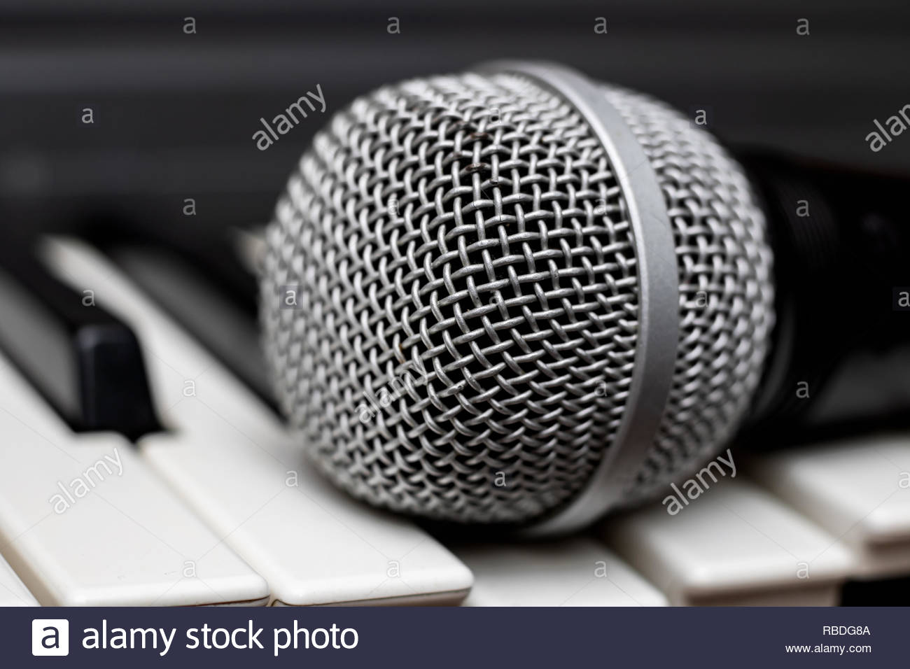 Microphone lies on the piano keys close up - Stock Image