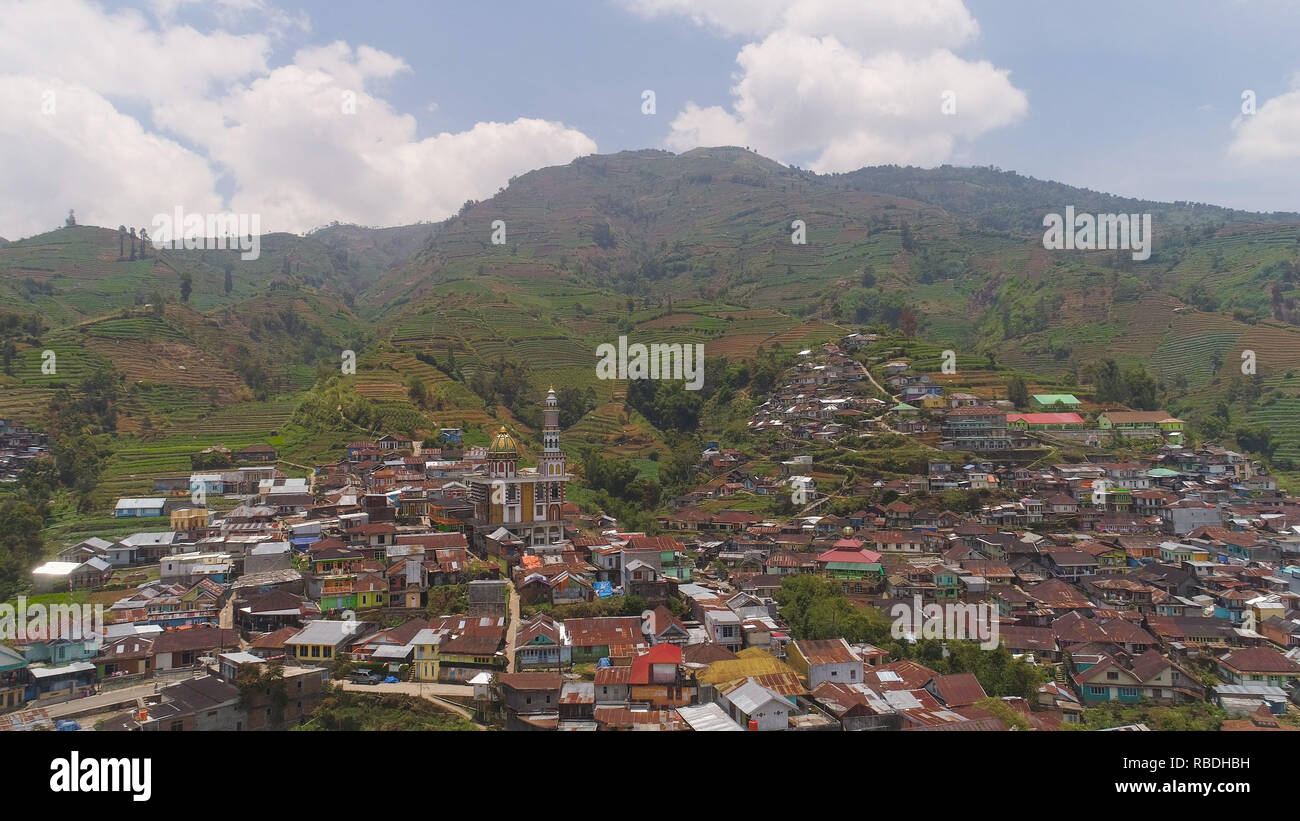 asian town with mosque in mountains among agricultural land, rice terraces. mountains with farmlands, rice fields, village, fields with crops, trees. Aerial view farm lands on mountainside. tropical landscape Java Indonesia. - Stock Image