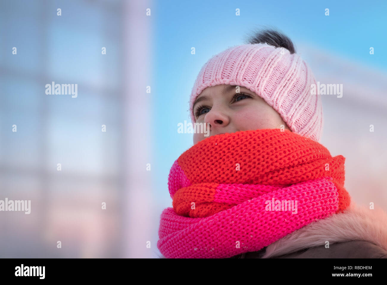 girl in a knitted hat with a bub and a fluffy hood looks ahead Stock Photo