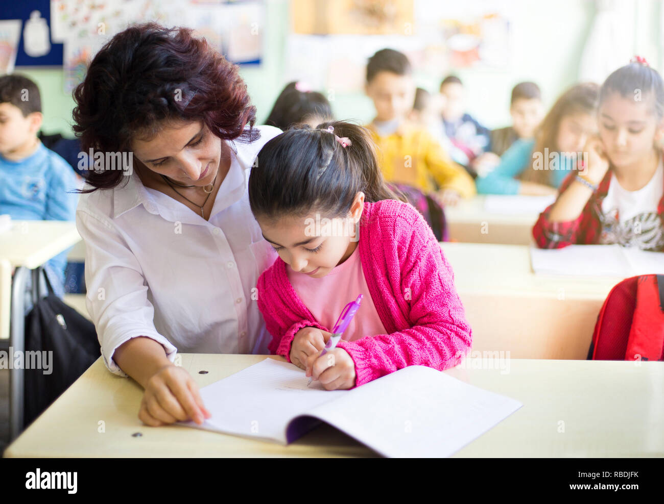 Teacher teaches to write to the girl student in the class - Stock Image
