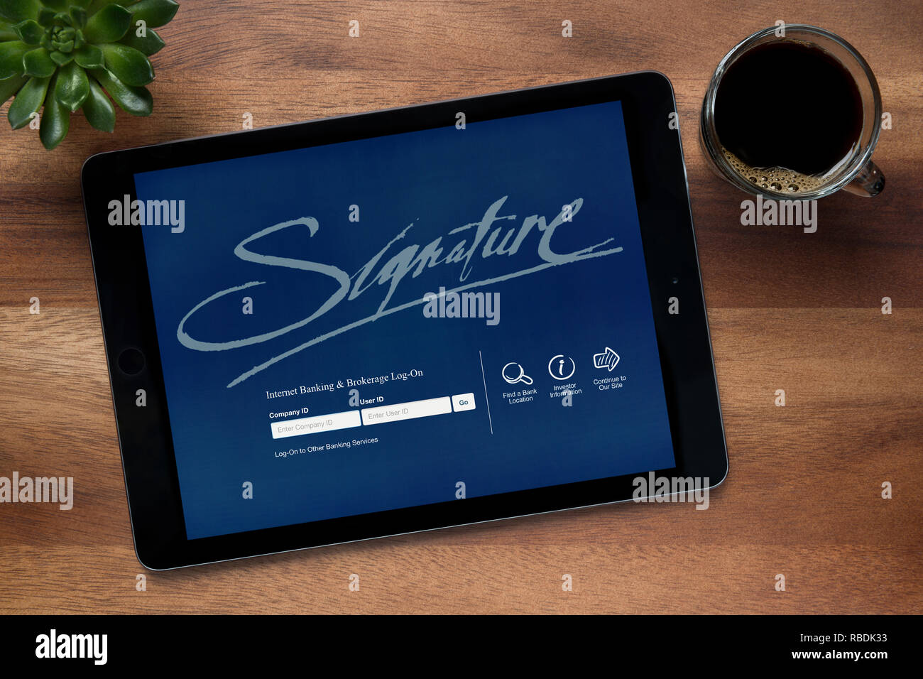 The website of Signature Internet Banking is seen on an iPad tablet, resting on a wooden table (Editorial use only). - Stock Image