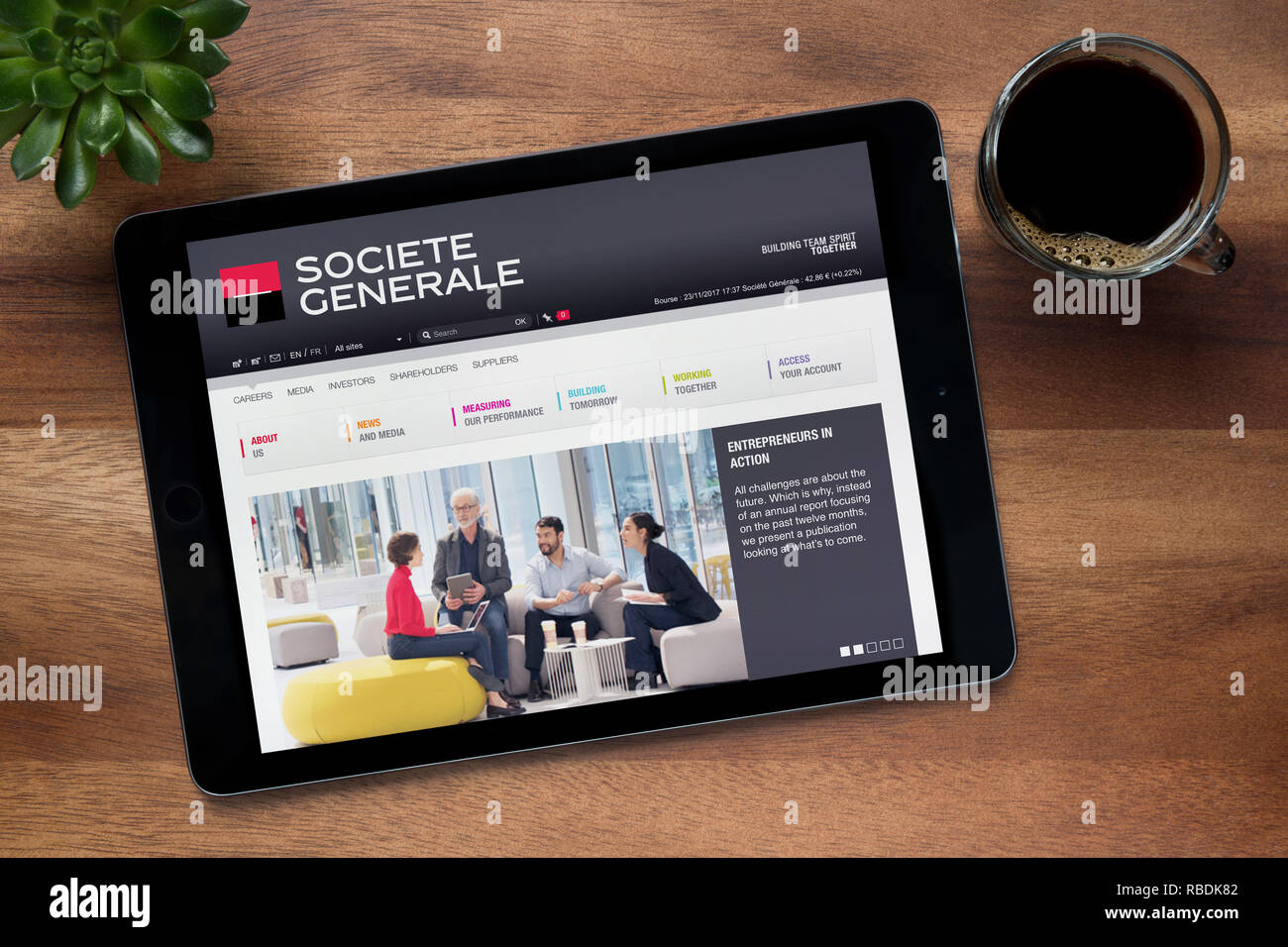 The website of Societe Generale is seen on an iPad tablet, on a wooden table along with an espresso coffee and a house plant (Editorial use only). - Stock Image