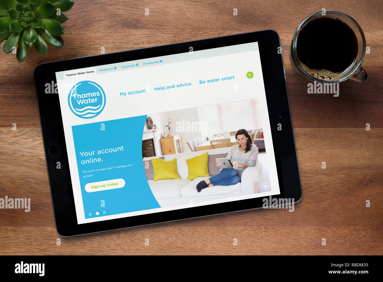 The website of Thames Water is seen on an iPad tablet, on a wooden table along with an espresso coffee and a house plant (Editorial use only). - Stock Image