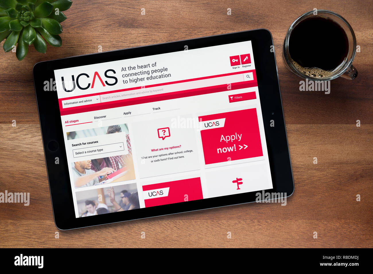 The website of UCAS (Universities and Colleges Admissions Service) is seen on an iPad tablet, resting on a wooden table (Editorial use only). - Stock Image