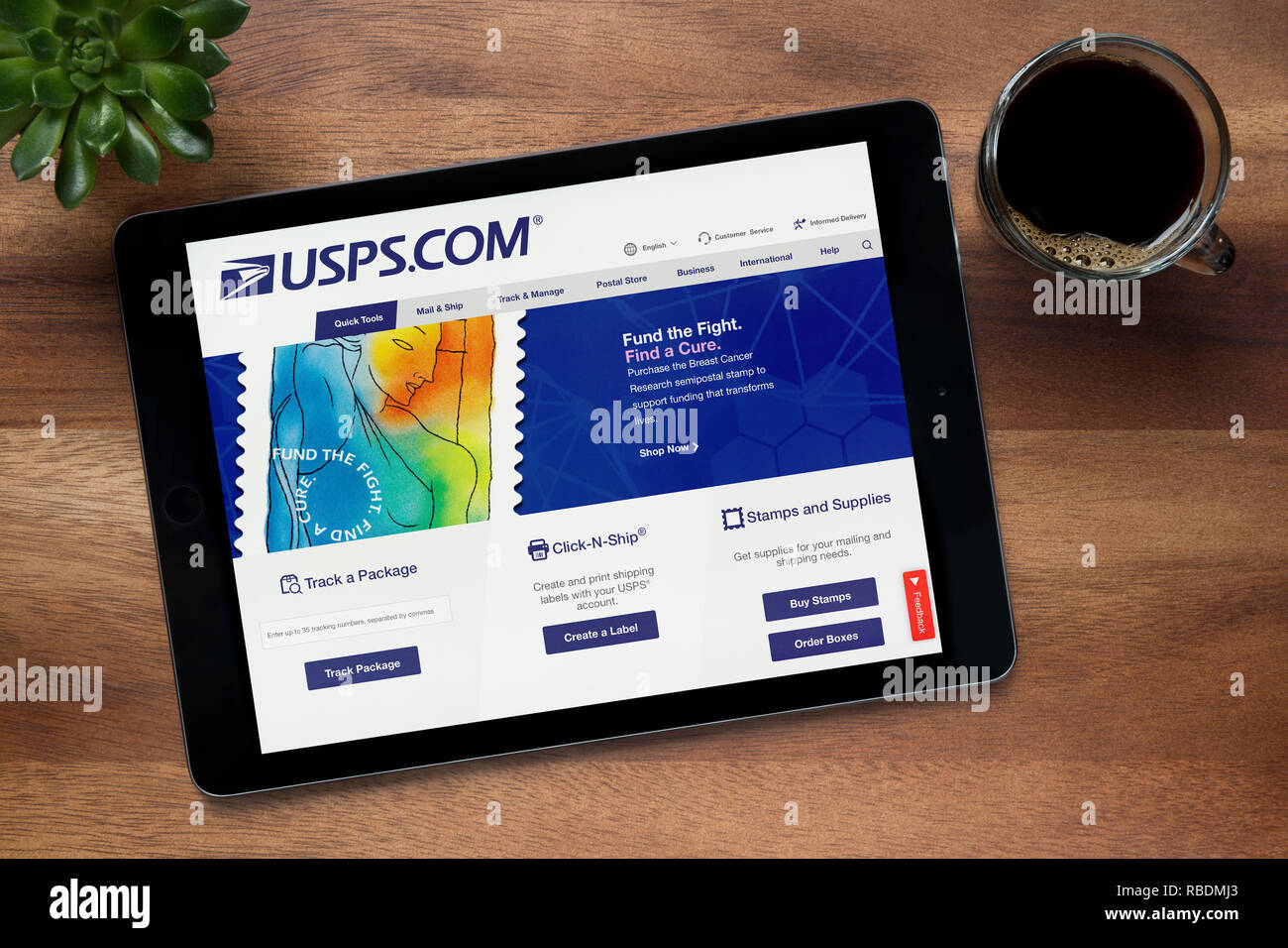 The website of USPS (United States Postal Service) is seen on an iPad tablet, resting on a wooden table (Editorial use only). - Stock Image