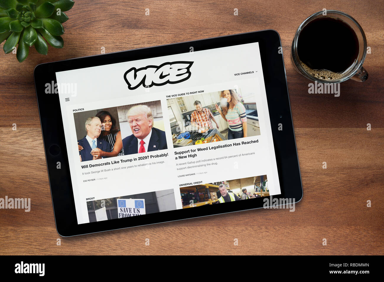 The website of Vice is seen on an iPad tablet, on a wooden table along with an espresso coffee and a house plant (Editorial use only). - Stock Image