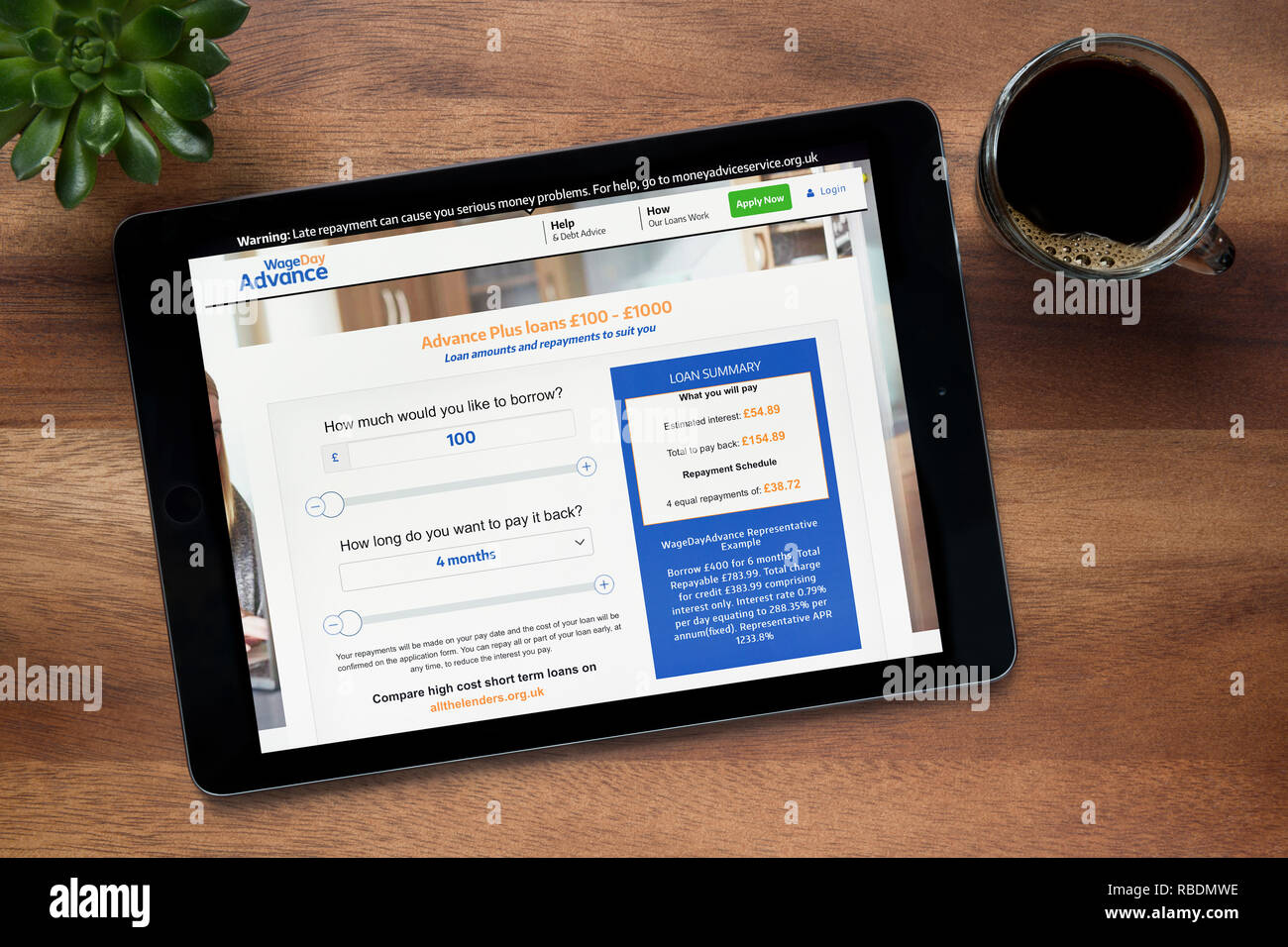 The website of Wage Day Advance is seen on an iPad tablet, on a wooden table along with an espresso coffee and a house plant (Editorial use only). - Stock Image