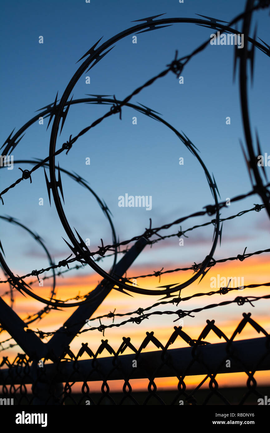Dramatic sunset with chain link fence and razor wire silhouette. - Stock Image
