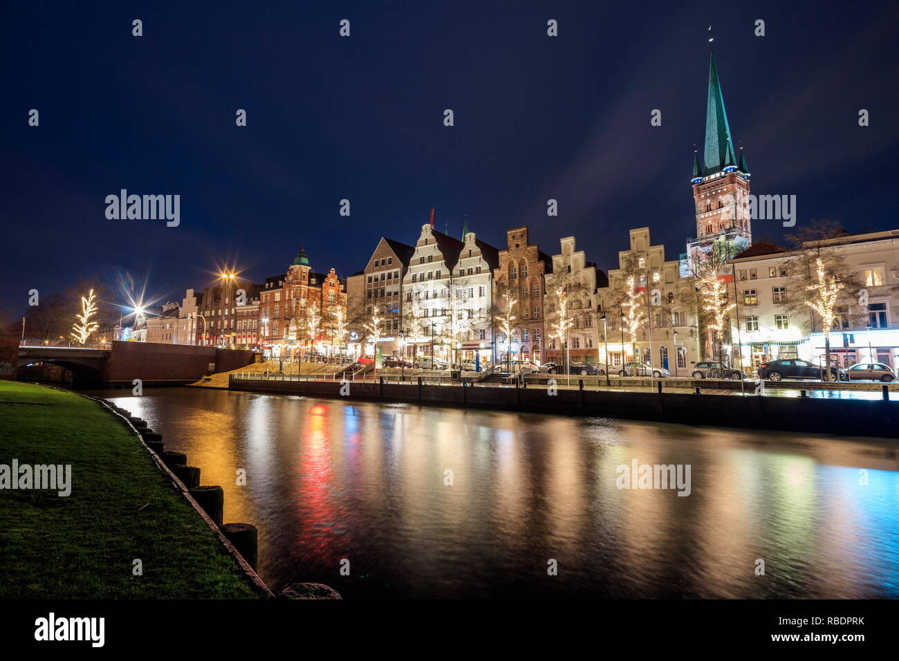 Night view of typical houses and the cathedral reflected in river Trave Lubeck, Schleswig Holstein Germany Europe - Stock Image