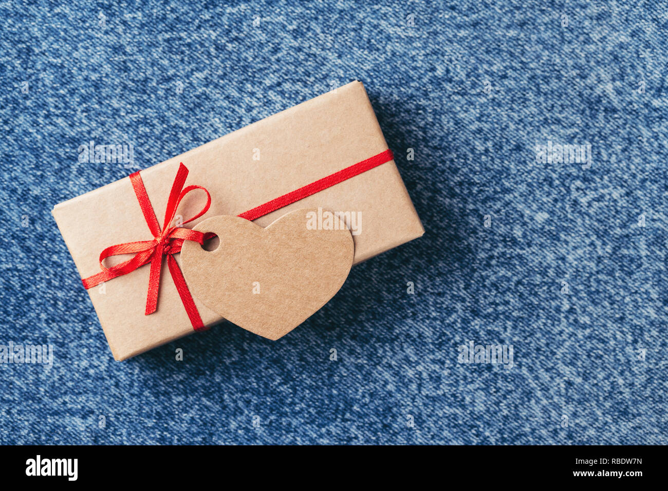 Kraft gift box with red bow and tag in shape of heart on blue jeans. Valentine's day card. - Stock Image