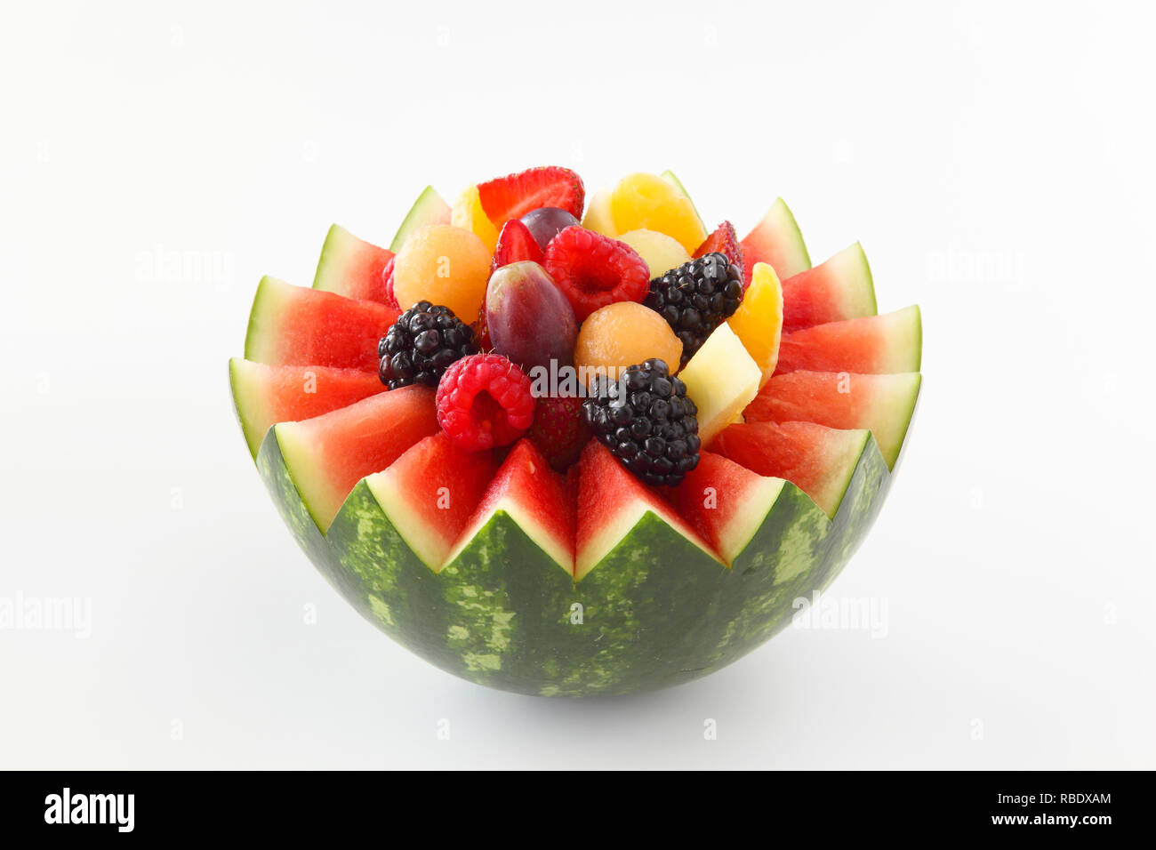 Fancy cut watermelon on a white background with assorted fruit inside like berries, grapes, pineapple, oranges - Stock Image