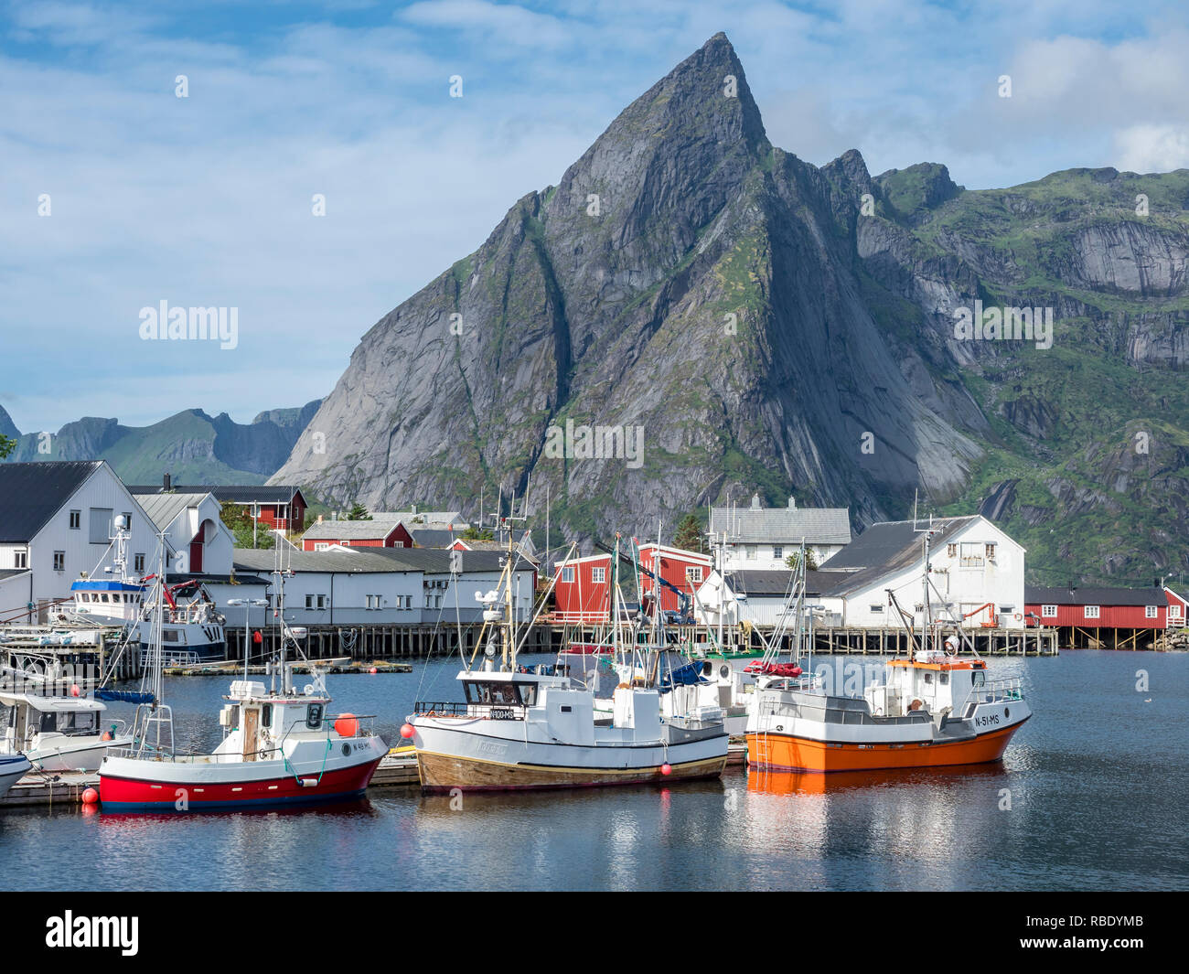 Fisherboats anchor in harbor of Hamnöy, steep mountan cliff of Olstinden in the back, island Moskenesoy, Lofoten, Norway Stock Photo