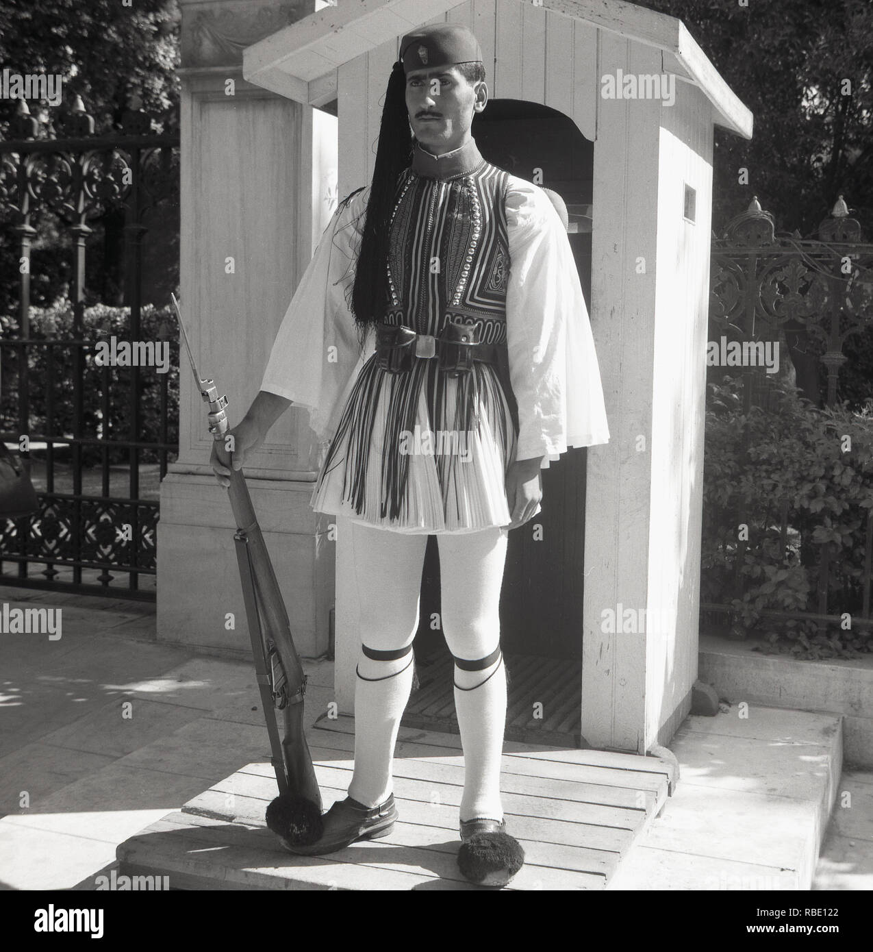 1950s, historical, Greek guard (Evzone) in full dress Uniform with rifle standing outside his sentry box, Athens, Greece. The Presidential Guard is a ceremonial infantry that guards the Tomb of the Unknown Solider and the Presidential Mansion in Athens. - Stock Image