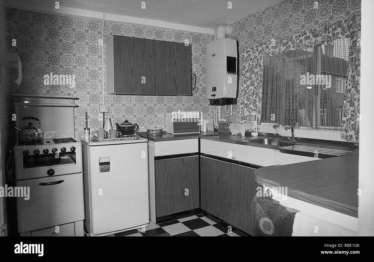 1970s, historical, view of a kitchen in a South London council flat, London, England, UK. The cupboards and work-tops are made from formica, a plastic laminate material, popular in this era as it was a hard-wearing, cost-effective material, with a surface that could be wiped over and hence easier to keep clean. - Stock Image