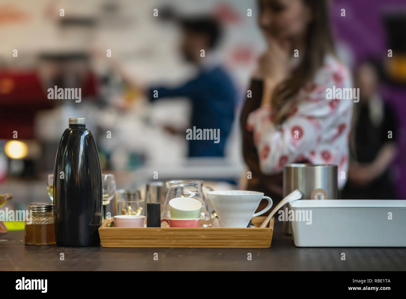 Set of dishes and accessories for the preparation of branded filtered coffee in the bar in the blurred background with unrecognizable girl barista - Stock Image