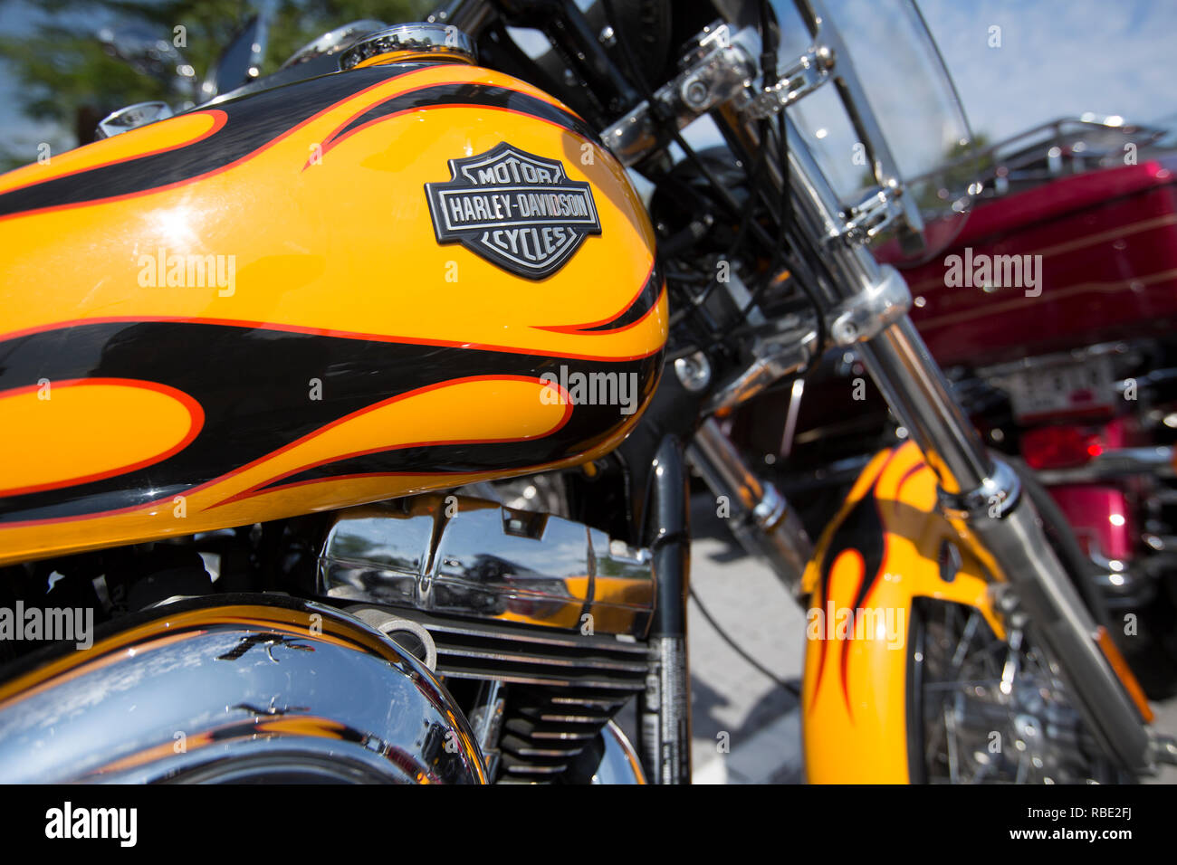 A closeup of a yellow Harley-Davidson gas tank with black and red painted flames and a classic Harley-Davison logo - Stock Image