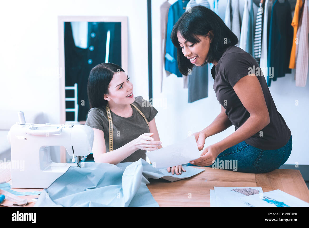Sharing ideas. Young seamstresses talking about creating new dress for their client - Stock Image