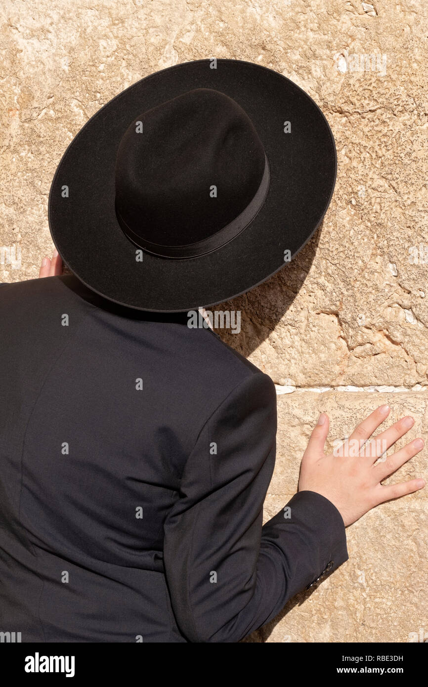 An irthodox Jewish man dressed in black prays at the Wailing Wall in the Old City of Jerusalem, Israel. - Stock Image