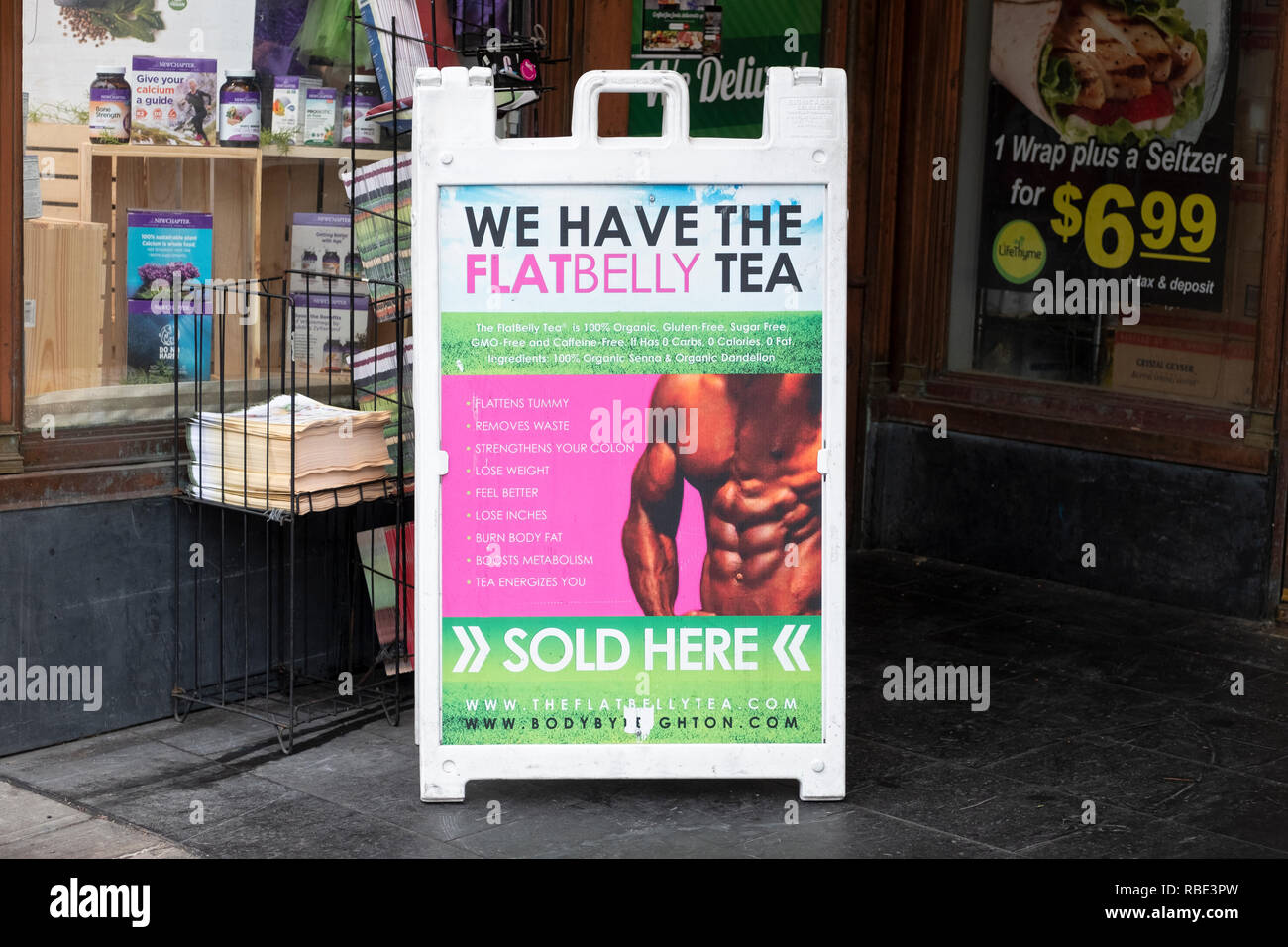 A sign outside the Lifethyme Natural Market advertising Flat Belly tea which purports to flatten stomachs, burn body fat, boost metabolism and more. - Stock Image