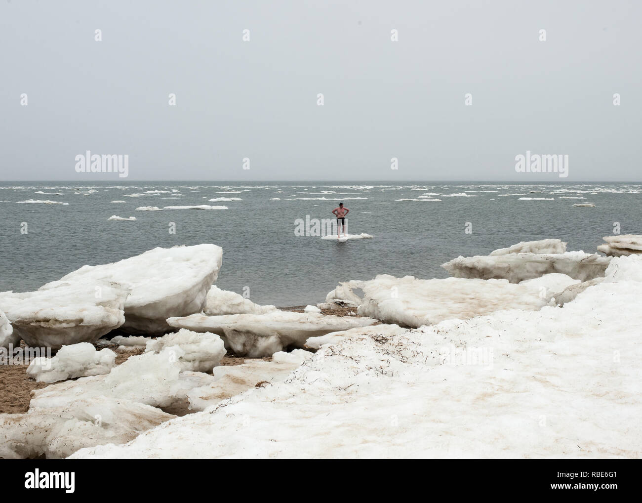 Boy standing on an iceberg out in the middle of Cape Cod Bay at Wellfleet, Massachusetts. - Stock Image