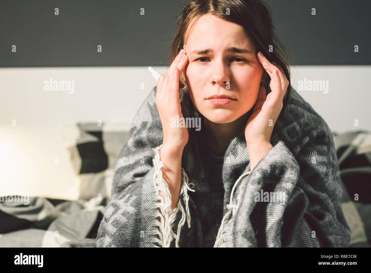 Subject disease and treatment. young Caucasian woman sits home bedroom bed wrapped in body blanket with high fever, fever holds strong headache behind Stock Photo