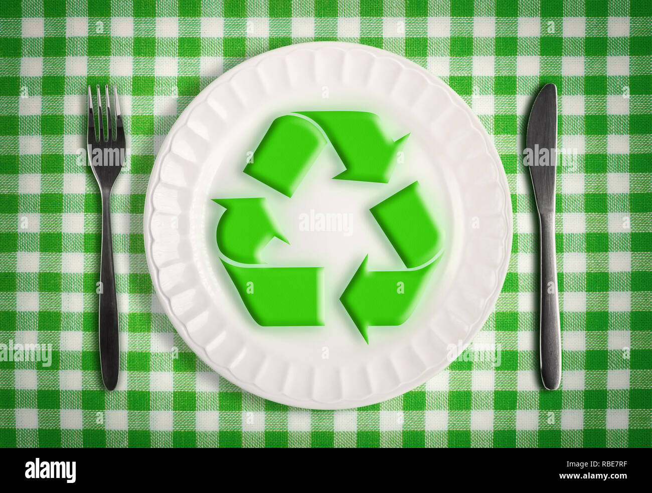 Autophagy with fasting concept, renewal symbol on plate with knife and fork on green table cloth, top view - Stock Image